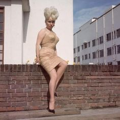 4.17 pm, Friday 13th 1977: always the glamazon, Dolores could only hope that the allure of her platinum updo and one-shouldered mini cancelled out the dreary background.