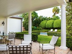 Brick patio with columns and iron furniture.  Views to pool and manicured boxwoods in Palm Beach, FL - design by Kara Mann