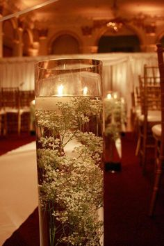 Very tall cylinders line the aisle with submerged baby's breath and floating candles which were later repurposed as centerpieces. Rustic Wedding Groomsmen, Rustic Wedding Seating, Rustic Wedding Colors, Rustic Wedding Showers, Dollar Tree Centerpieces, Floating Candle Centerpieces, Fall Wedding Centerpieces, Tall Centerpiece, Wedding Tables