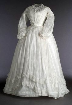 Two-piece dress, ca. 1860. White cotton muslin over white cotton taffeta. Bateau neckline front & back, decorated with lace. Hook closure in front. Museo del Traje
