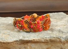 The red orange heart shaped Mexican fire opal is one heart stopping focal! The brass, amber, red and orange beads compliment the heart focal and would make a heart felt gift just for her. The bracelet is unique and would be a lovely accessory for any eclectically conscious woman. Its a passion working with seed beads, using a needle and thread to create something wonderful, one bead at a time. There are no actual patterns, it all happens rather organically and color drives the whole process…