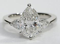 Exceptionally crafted, this diamond engagement ring showcases two beautifully matched pear-shaped diamonds prong-set in platinum to frame your center diamond. 1/2 carat total diamond weight.