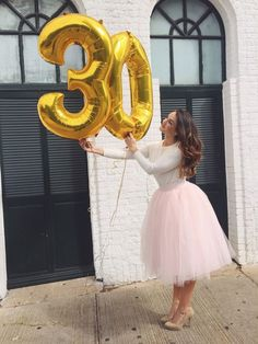 mujer con vestido rosa de tutu cargando globos de numero 30