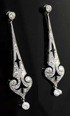 A pair of Belle Epoque unmarked white gold and diamond drop earrings, of tapering, pierced and scroll design with a millegrain setting.