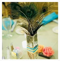 peacock feather centerpiece...i like this but maybe with some white feathers added in and lace wrapped around the vase