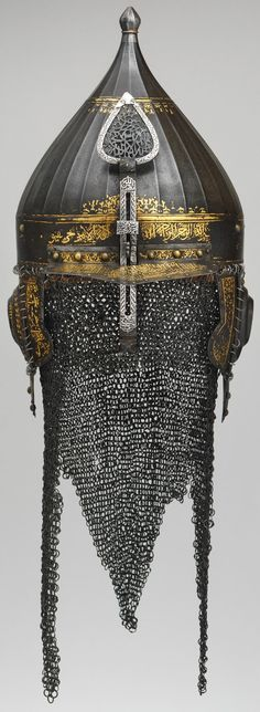 Ottoman chichak type helmet, 16th century, steel, gold, silver Dimensions: H. 10 3/4 in. (27.8 cm); Wt. 5 lb. 11 oz. (2580 g), Met Museum, forged from watered steel and decorated in gold with arabesques and Koranic inscriptions.