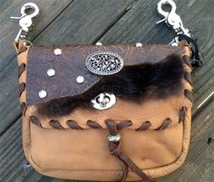 BUFFALO - Made from buffalo & features buffalo hair-on-hide, printed leather & crystal studs. Silver centerpiece sparkles with stones & flap is accented with a chocolate brown leather whip stitch. All bags have been recycled and reinvented, and embellished. Bag can be clipped onto belt loops for hands-free carrying of your essentials. Has exterior pocket on the back & includes a leather strap inside, which gives this bag great versatility. Add the strap when you want a completely different…