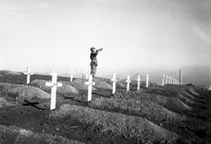 Marines of the 1st Marine Division pay their respects to the fallen during memorial services at the division's cemetery at Hamhung, Korea, following the break-out from Chosin Reservoir/13 December 1950.