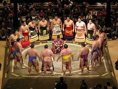 Sumo wrestlers gather in a circle around the gyōji (referee) in the dohyō-iri (ring-entering ceremony).