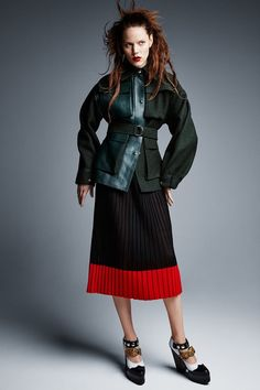 The brunette model wears Celine wool and leather jacket with pleated Salvatore Ferragamo skirt and Mulberry heels
