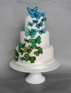 Butterfly Wedding Cake - Cakes by Natalie Porter - Hertfordshire and Essex. Featuring an ombre cascade of butterflies in blue, turquoise and green, this wedding cake is simple and  feminine, whilst also colourful.Each butterfly is hand made from icing, and so can be produced in any colour to suit your theme