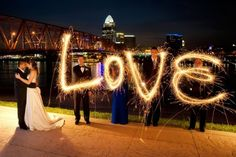We could do this after the reception, once it gets dark! You and Camrin would have to stand very still, and the people with the sparklers would stand still besides moving the sparklers to write their letter. We would put the camera on a tripod and set the exposure to maybe like 30 seconds or a minute. Might take a few tries, but I think it would be worth it :)