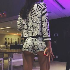 In a black and white, floral-embroidered suit that cheekily showcases her underbutt.   - MarieClaire.com