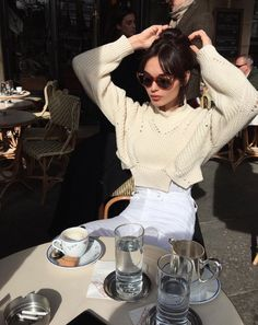 French Inspired Style: Cropped sweater, high waist white denim jeans, cat eye sunglasses, sitting at a cafe.