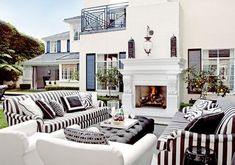 Prepster Stripe    An open air fireplace is given a preppy look when accented by big, bold black and white stripes and geometric pillows.