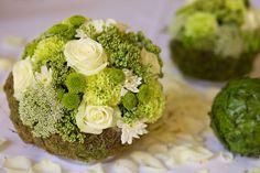 Kugelförmige Tischdekoration in den Farben weiß und grün.