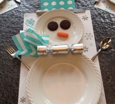 Snowman Place setting for kids Christmas table...chocolate covered mint Oreos for eye, carrot for nose, party cracker & cocktail napkin for scarf, cocktail napkin for hat. Fork & spoon for arms, knife for hat brim.