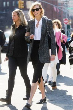 "When it's time to get down to business, Kloss dresses the part. While running around New York the day of the Michael Kors runway show, Karlie donned an ensemble not unlike your office staples: tweed blazer, crisp button-down, and tailored trousers.  Granted, both the blouse and pants were cropped — but, that's just the model interpretation of a ""business casual"" dress code. Karlie is wearing a Jonathan Simkhai shirt and Chanel bag"