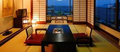 Modern Japanese design dining space and sliding doors revealing sweeping city panoramic views. ~  さくらや旅館、熱海温泉