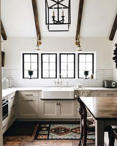 Kitchen with wood beams. Kitchen with vintage runner. Love the overall style of this kitchen with black window frames.