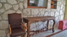 Livingroom feature stone wall with build-in niches for Flat Screen TV and other electronics or entertainment center. Hacienda del Río Custom Homes. Playa del Carmen real estate area.
