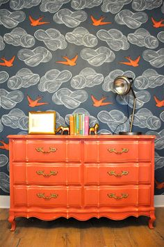 Vivid orange dresser against the backdrop of a very imaginative wallpaper