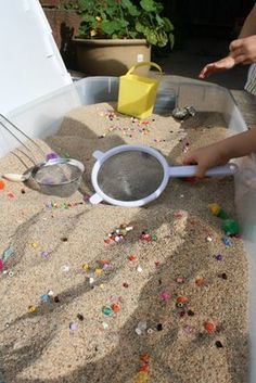 Putting beads in the sandbox, along with sifter.