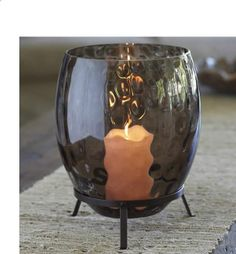 """TWILIGHT MIST™ HURRICANE Was $80 Now $35 While Supplies Last  Dramatic glass hurricane reveals a moody gray color and unique textured surface when lit by a pillar candle, Escential jar or tealight tree, sold separately. Presented on a footed metal stand. Includes leveling beads to stabilize pillar. 10""""h, 6¾""""dia.  http://www.partylite.biz/legacy/sites/stevengerard/productcatalog?page=productdetail&sku=P91056&categoryId=55268&showCrumbs=true"""