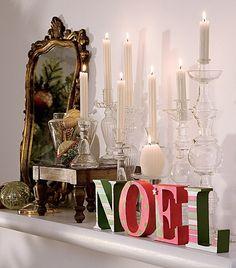 Natal é uma época de exageros. Se você gosta de velas, espalhe-as por toda a casa. Aqui, estão no aparador em castiçais de diversos tamanhos e junto com outros elementos natalinos