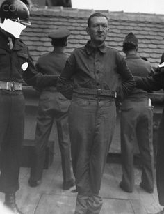 Hanging of Gronwaldt. After the Nuremberg war crimes trials, convicted Nazi war criminal Karl Gronwaldt stands on the gallows, about to be hanged, ca. 1946. The photo has been altered to hide the identities of the guards next to him.