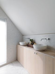 Fresh and clean bathroom in bright oak with marble sinks. We love the walls covered with marble tiles.