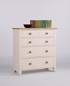 New England Painted Chest Of Drawers This is a beautiful chest of drawers Clean fresh lines and lightly painted in ivory  It has three large deep drawers With two smaller drawers above The drawers are tongue and groove With contrasting wooden knob handles The top is solid ash that has been lightly lacquered This is a satin finish which is resilient and serves to protect the natural beauty of the ash The drawers are finished in a knock resistant paint in ivory