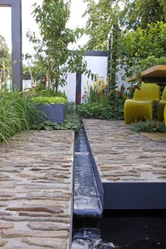 Rill runs between river rock in concrete patios, one of which is elevated a bit over the other -  Garden Design London and South East
