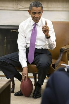 President Barack Obama holds a football as he meets with senior advisors in the Oval Office.
