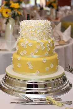 Yellow and white daisy wedding cake..How cute is this yellow wedding cake covered in daisies? This is the perfect choice if you don't want formal fresh flowers or you feel like roses are too dressy for you.