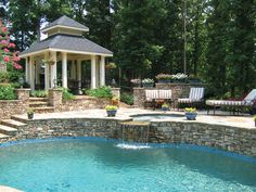 Pool with stacked stone retaining wall, gazebo, flowering planters and landscaping | Anthony and Sylvan Pools