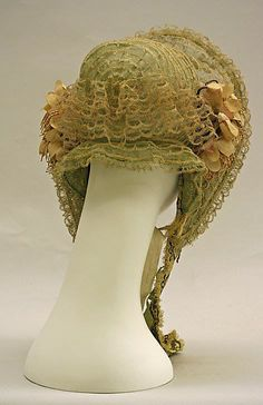 Straw bonnet, edged in a braid tape, ruched lace facing with flower trim at jawline, functional ties. American. ca 1856. MET
