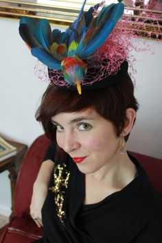 Vintage 1940s-style black felt tilt hat with colorful faux parrot (made from naturally-shed parrot feathers) surrounded by pink/purple/green vintage veiling.