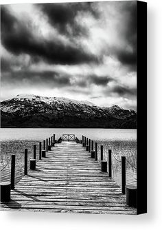 Black and white conversion of a photo of a dock whose lines point towards a beautiful landscape with snowy mountains under a dramatic cloudy sky in San Carlos de Bariloche, Río Negro, Argentina. The image gets printed onto one of our premium canvases and then stretched on a wooden frame of stretcher bars. Click through the image to customize your print for your home or office! Travel art for your wall by Eduardo Jose Accorinti.