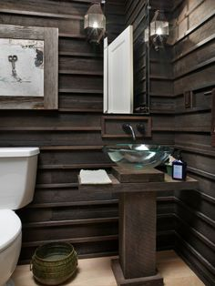 Bathroom with walls of salvaged yellow pine finished with ebony stain. I like the bold and chunky pedestal sink base, and the glass basin sink.