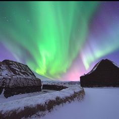 An aurora borealis illuminates a starry sky in Iceland.
