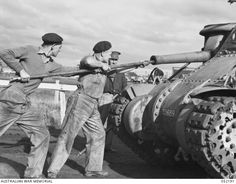 MELBOURNE, VIC. 1943-06-02. PERSONNEL OF M.T. VEHICLE PARK, GROUP 1A CLEANING OUT THE 75 MM M3 GUN OF A GRANT M3 MEDIUM TANK.