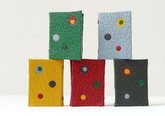Mini-livres reliés en cuir avec incrustation de ronds. Couleurs : jaune, rouge, gris, vert, bleu clair
