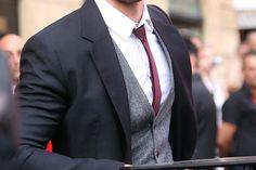 Grey vest, blue jacket, red tie, white shirt