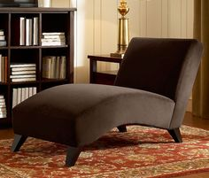 Enhance your home decor with this unique chaise lounge chair. This fashionable piece of furniture features a dark brown, velvety fabric upholstery and espresso stained, non-mar foot glides.