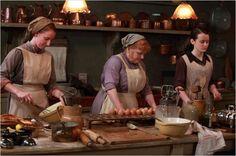 A cozinha onde as refeições eram preparadas. Uma fantástica coleção de panelas e formas de cobre. Mrs Patmore, Daisy e suas ajudantes.