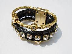 Pulseira confeccionada em couro trançado preto e dourado com entremeios dourados de strass, fio de strass e finalizada com fecho magnético dourado.     **Outras cores disponíveis