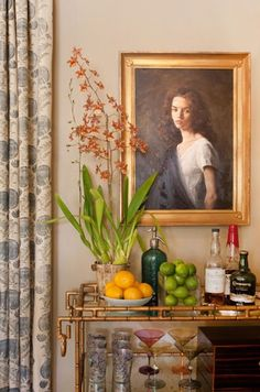 gilded bamboo-motif bar cart, gold-frame portrait, bright citrus, orchid, subtle print on curtains, vintage barware & multicolored martini glasses