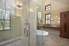 This bathroom features a central glass shower with entry on both sides, adjacent white pedestal bath tub , and dark wood cabinetry.