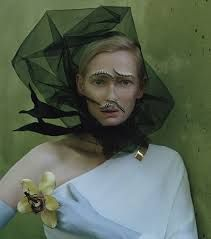 Muse for avant garde designers and photographers alike, Tilda Swinton is styled to herald in spring with live centipedes as face accessories and a yellow flower ring in bloom; black net hair adornment; white single shoulder top with gold shoulder clasp jewellery ...  cover shoot photo for W magazine,   May 2013